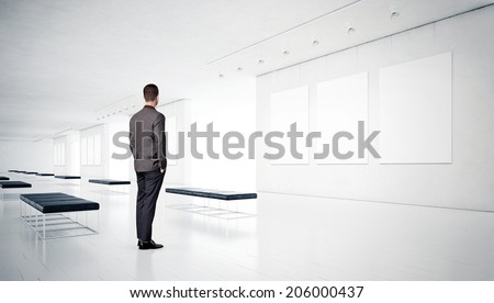 Gallery room and man looking at frames - stock photo