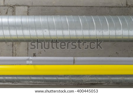 galvanized, grey and yellow pipes, ventilation and water and gas system - stock photo