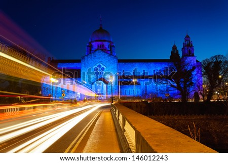 Galway Cathedral lit up blue at night and car lights trails - stock photo