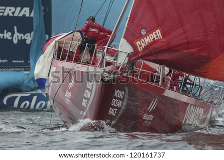 GALWAY, IRELAND - JULY 7: Unidentified crewman on bow of Camper Emirates Team New Zealand brings in spinnaker during In-port race of 2011-2012 Volvo Ocean Race in Galway, Ireland on July 7, 2012. - stock photo