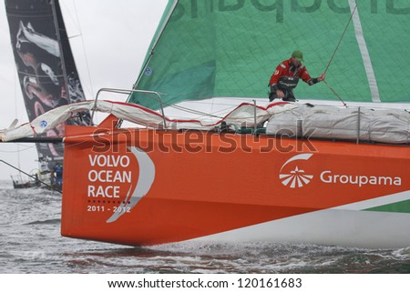 GALWAY, IRELAND - JULY 7: Unidentified foredeck crewman on bow of France's Groupama during In-port race of 2011-2012 Volvo Ocean Race in Galway, Ireland on July 7, 2012. - stock photo