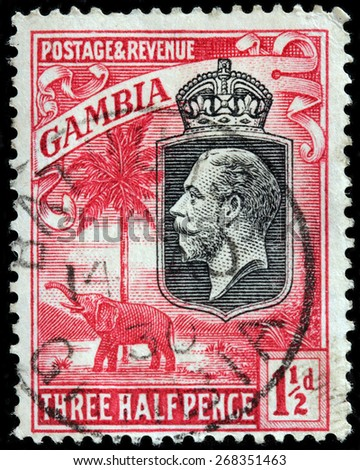 GAMBIA - CIRCA 1922: A stamp printed by GAMBIA shows image portrait of King Georg V against African landscape with elephant and palm tree, circa 1922 - stock photo