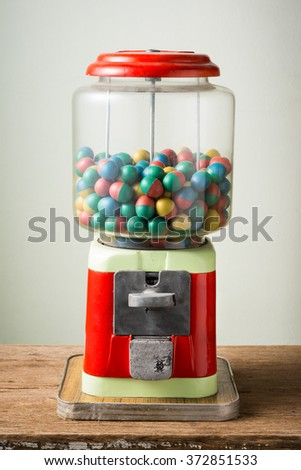 gamble eggs in vintage coin operated gumball machine on old wood - stock photo