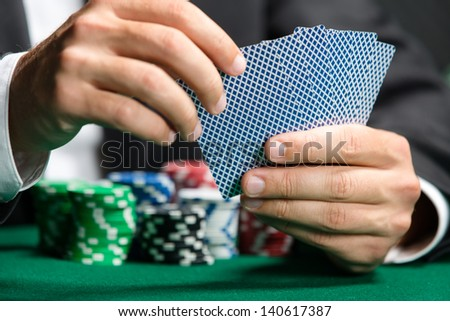 Gambler playing poker cards with poker chips on the table. Risky entertainment of gambling - stock photo