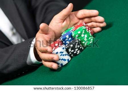 "Gambler stakes ""all in"" pushing his chips forward. Risky entertainment of gambling - stock photo"