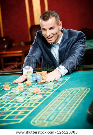 Gambler stakes playing roulette at the gambling house. Risky entertainment of gambling - stock photo