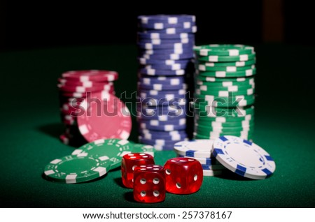 Gambling chips and dices on green table - stock photo