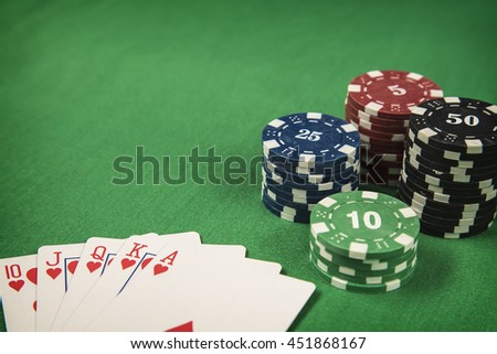 Gambling chips and poker card on green felt background - stock photo