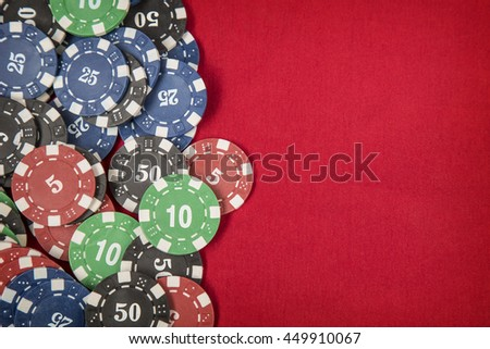 Gambling chips for poker on red felt background - stock photo