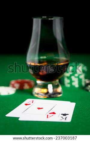 gambling, fortune and entertainment concept - close up of casino chips, whisky glass, playing cards and cigar on green table surface - stock photo