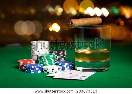 gambling, fortune and entertainment concept - close up of casino chips, whisky glass, playing cards and cigar on green table surface over holidays night lights background - stock photo