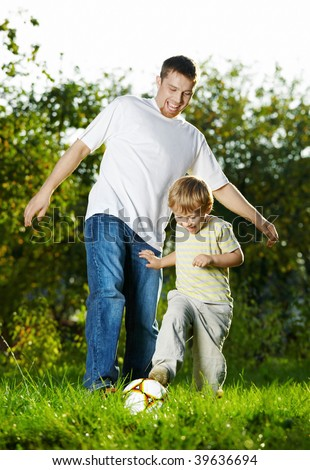 Game in football of father and son on a summer lawn - stock photo