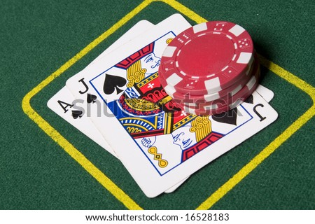 Game of blackjack at a casino with chips on a green blackjack table - stock photo