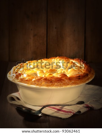 Game pie in serving dish on rustic background with spoon - stock photo