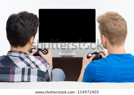 Gamers with joystick. Rear view of two young gamers playing video games - stock photo