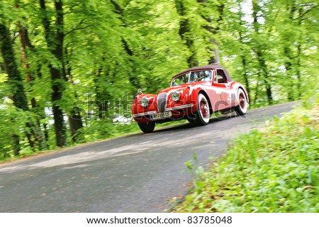 """GAMLITZ, AUSTRIA - APRIL 30: An unidentified driver in a 1953 Jaguar XK 120 DHC participates in a rally for vintage cars """"Suedsteiermark Classic"""" on April 30, 2011 in Gamlitz, Austria. - stock photo"""