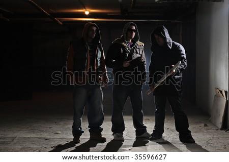 Gang members in a dark alley - stock photo