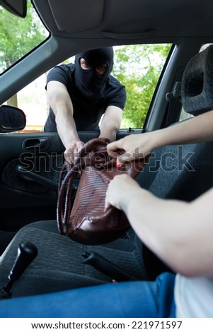 Gangster attacks women in car and take her bag - stock photo