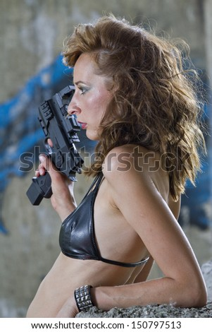 Gangster Woman with handgun in profile, posing outdoor - stock photo