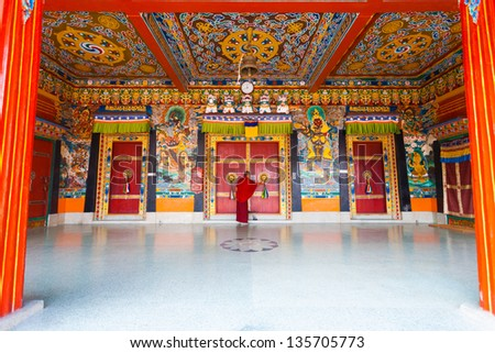 GANGTOK, INDIA - JANUARY 12: A monk locks the colorful entrance doors of the Rumtek Monastery, a tourist attraction and home of the Karmapa on January 12, 2008 in Gangtok, India - stock photo