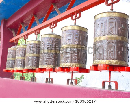 GANGTOK, SIKKIM/ INDIA-JUNE 12: Row of Brown Prayer Wheels at Enchey Monastery for Buddhist turning and praying on June 12, 2012 in Gangtok. Enchey Monastery is among Sikkim's famous monuments. - stock photo