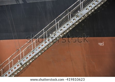 Gangway ladder on black and orange iron ore carrier - stock photo