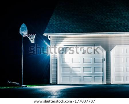 Garage and basketball hoop at night. - stock photo
