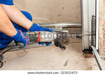 Garage doors installation. Worker drills a hole for the bolt - stock photo