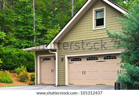 Garage doors on a modern house.  Double doors, with windows, on one side and an offset single beside it. - stock photo