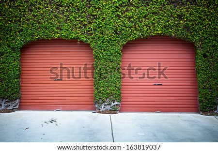 garage doors surrounded by green leaves - stock photo
