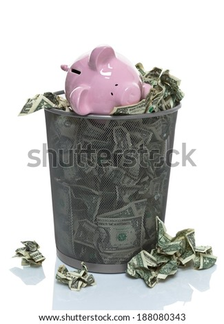 Garbage can full of money spilling over front view - stock photo