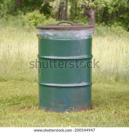 Garbage can on grass in park. - stock photo