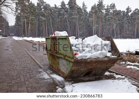 Garbage container in a snowy park - stock photo