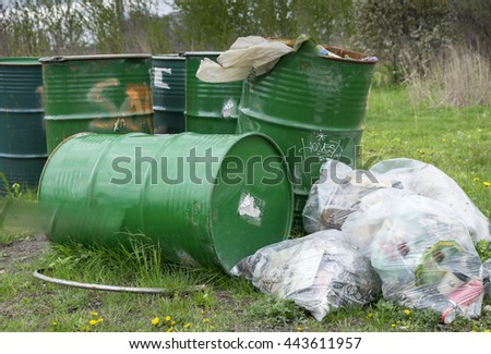 Garbage in plastic bags beside green metal garbage cans in a park in Toronto Canada. - stock photo