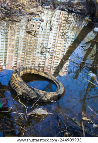 Garbage, old tire and reflection of the high-rise in the water on the landfill. - stock photo