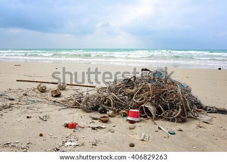 Garbage, plastic, wood and trawl on the beautiful beach - stock photo