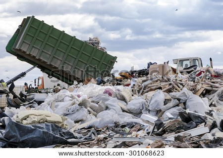 Garbage truck unloads garbage from container at the dump - stock photo
