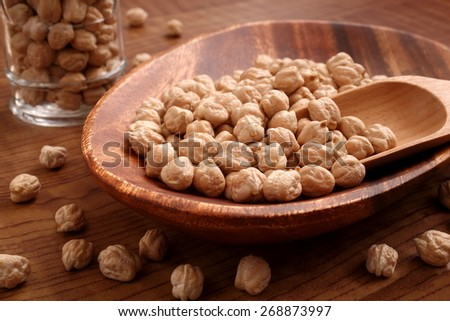 garbanzo  beans on woody plate - stock photo