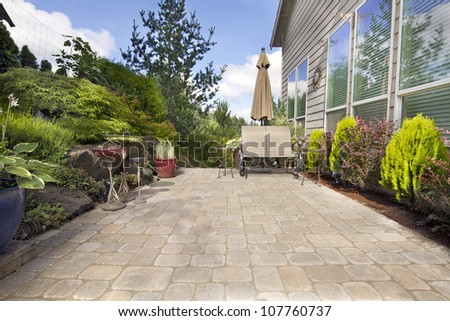 Garden Backyard Paver Patio with Chairs Umbrella Plants Pots Trees and Decoration - stock photo