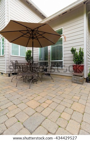 Garden Backyard with brick paver patio and furniture with table chairs and umbrella - stock photo