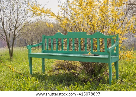 garden bench with spring yellow flowers - stock photo