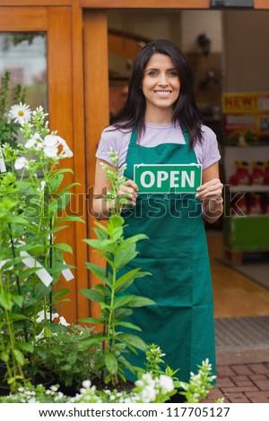 Garden center worker holding open sign at entrance to garden center - stock photo