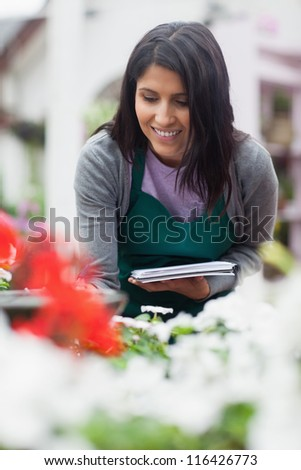 Garden center worker looking at the flowers and making notes and smiling - stock photo