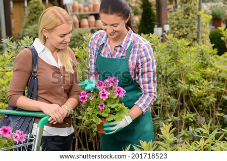Garden center worker showing customer woman potted flower - stock photo