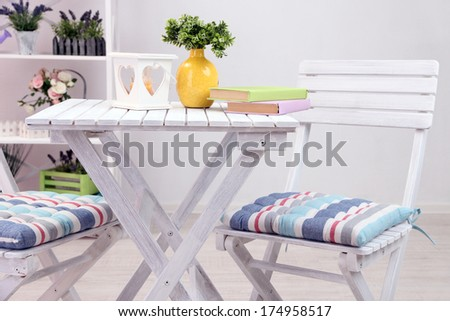 Garden chairs and table with flowers on shelves on white background - stock photo