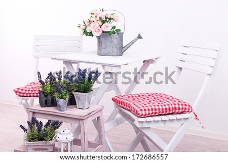 Garden chairs and table with flowers on wooden stand on white background - stock photo