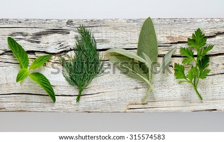 Garden culinary aromatic herbs on a weathered board, top view - stock photo