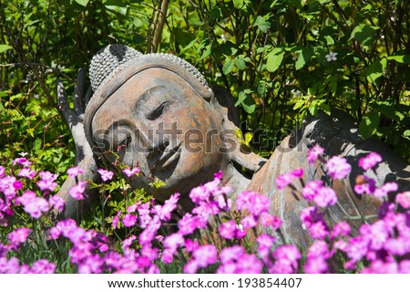 Garden decoration with a lying buddha. - stock photo