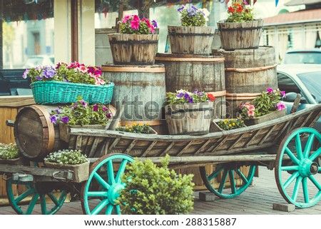 Garden flowers in different pots on old cart. Toned picture - stock photo