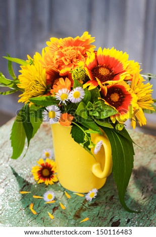 Garden flowers in yellow vintage mug - stock photo